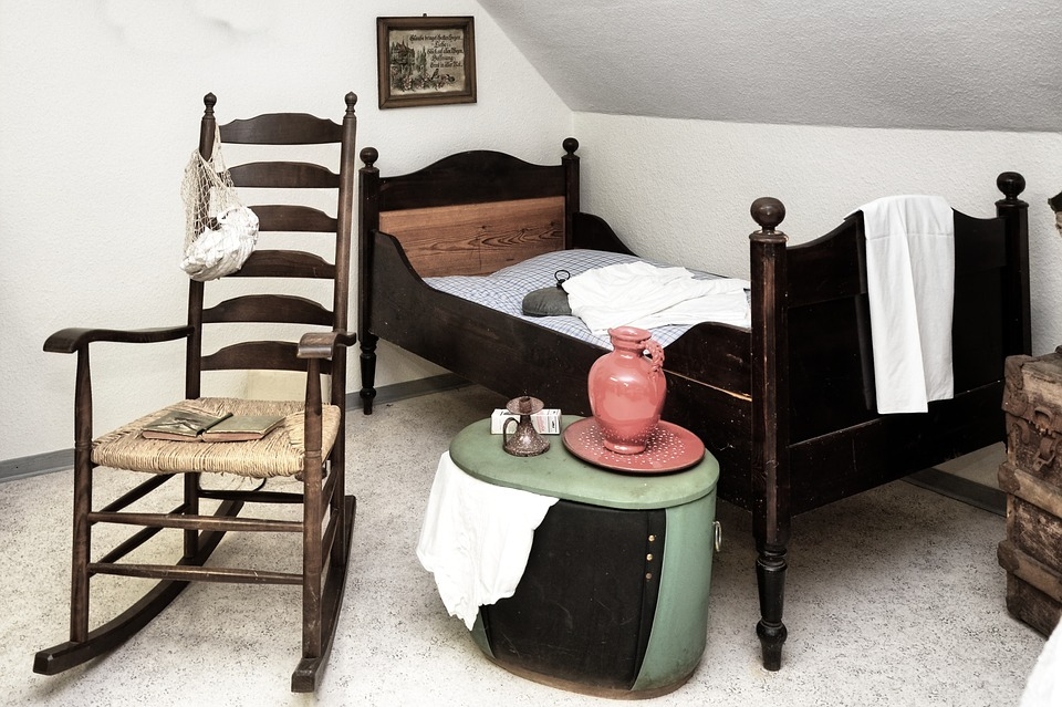 history of rocking chairs - old rocking chair with bed, trunk and old pottery